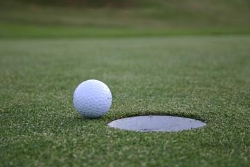 balle de golf devant un trou