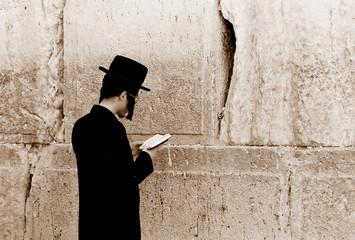 jew is praying by the western wall, jerusalem