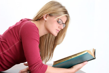 beautiful young woman in glasses reading book