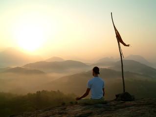 man meditating at sunrise