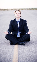 young businessman practices meditation in the midd