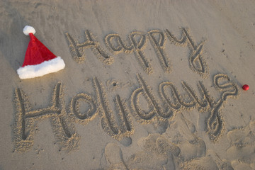 happy holidays written in sand