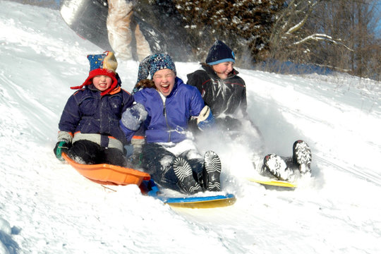 three kids sledding