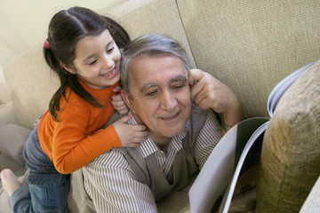 girl and grandfather reading