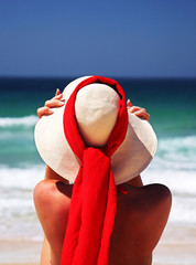 girl sitting on sandy beach in the sun adjusting hat. blue sky,