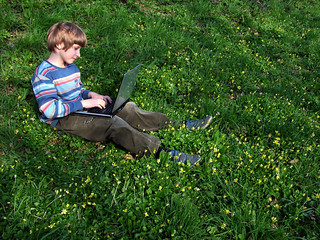 child with notebook sit green grass