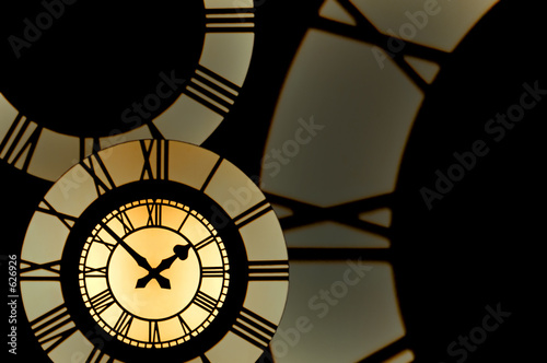 gold clockface surrounded by parts of roman numeral clockfaces