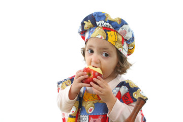 little girl eating an apple dressed as a chef