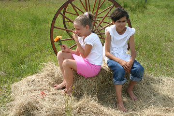 boy and girl on hay with flowers