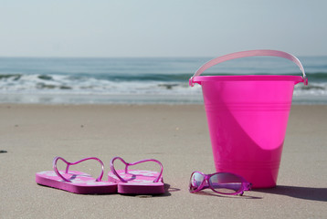 flip-flops, sunglasses and pail on the beach