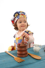 little girl cooking dressed as a chef