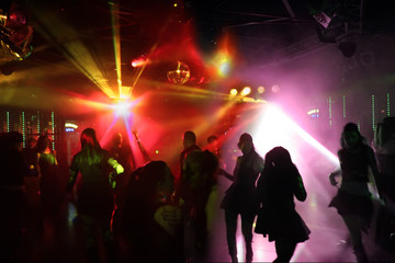 tanzende junge menschen im rot/violettem licht