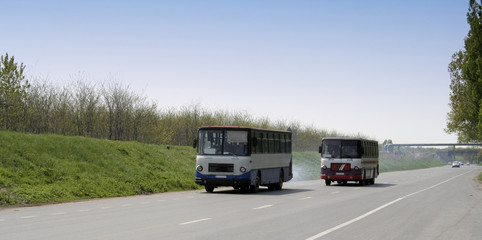 two old busses on the road