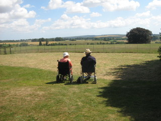 elderly couple relaxing in wheelchairs in the sun
