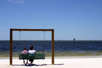 couple sitting on a swing at the beach