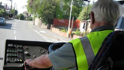 an elderly man driving a bus.driving bus/transport