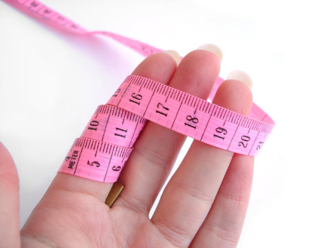 hand with pink tape measure against white background