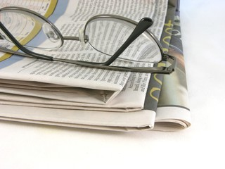 glasses on newspapers