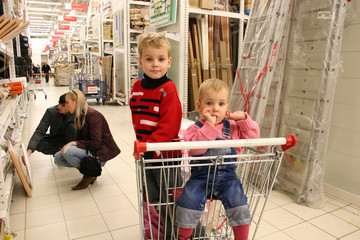 children in shopingcart and couple