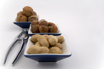 walnuts, hazelnuts and peanuts in three bowls