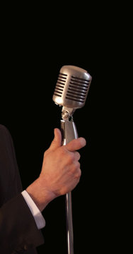 singer holding vintage microphone & stand