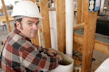 plumber working in toilet tank