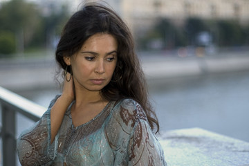 young brunette posing beside river on city bridge