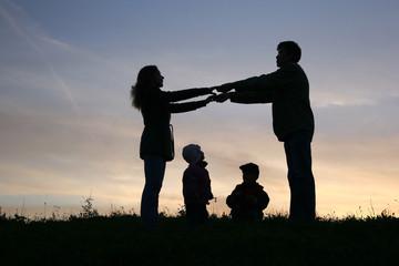family of four on sunset sky