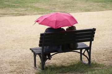 frau auf einer bank mit regenschrim in pink