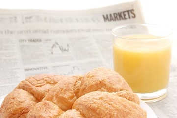 fruit juice, croissant and business pape