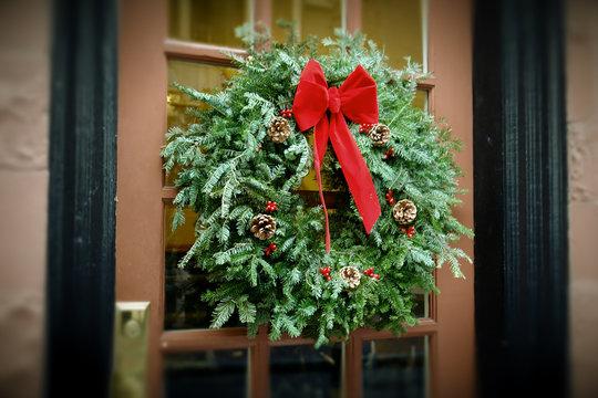antiqued christmas wreath hanging on door