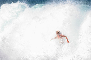 young surfer rides out crashing waves