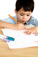 a young boy engross in his drawing