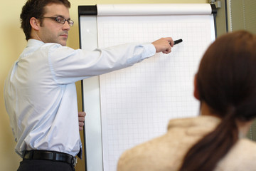 man explaining an idea on flip chart to woman