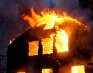 wooden house in flames