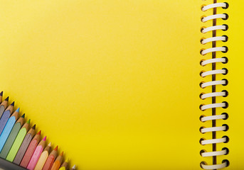yellow spring notebook and crayons in a corner.