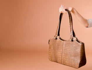 hand holding leather handbag on the beige backgrou