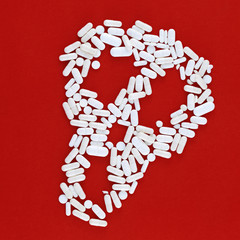 skull made of white pills on a red background