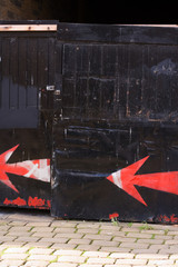 spray painted arrow on black gate