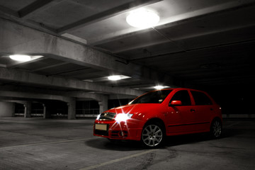 red hatchback car on black and white background