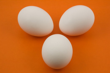 three white eggs on orange