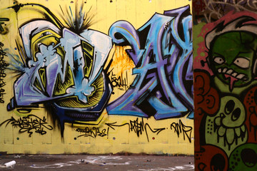 graffiti tags that are yellow and blue