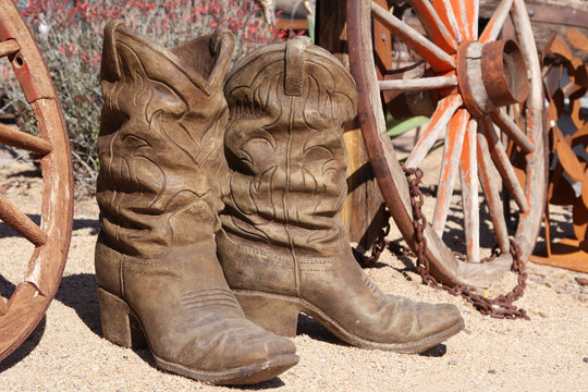 clay cowboy boots and antique wooden wagon wheels