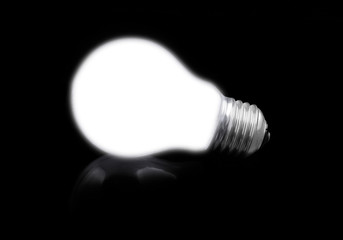 close-up of lit light bulb on black