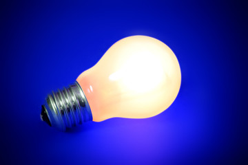 illuminated lightbulb on blue background