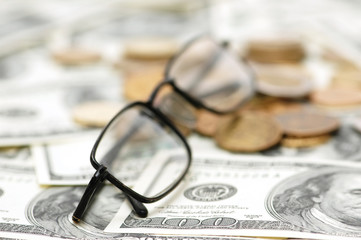 reading glasses with coins and dollar bank notes