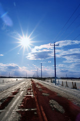 cold icy winter road in sunny scene