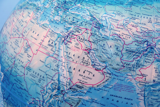 closeup of world globe focused on middle east with blue backgrou
