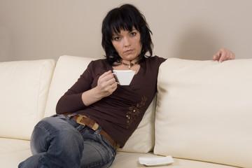 beautiful woman on the sofa drinking coffee