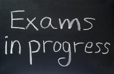 exams in progress, written on a school blackboard.